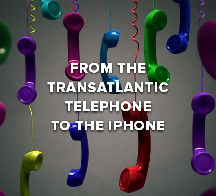 different colored telephone receivers hanging by cords in the air